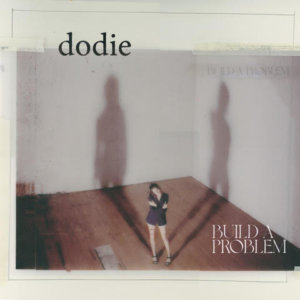 Soundtracked by a delicate alt pop sound, Build A Problem is dodie owning her vulnerability